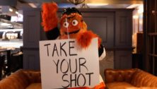 """Gritty, holding a """"Take Your Shot"""" sign, will be visiting Radnor High for a Flyers vaccine promotion."""