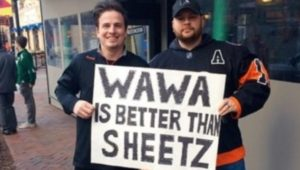 Convenience stores battle it out. Two men hold a Wawa is Better than Sheetz sign