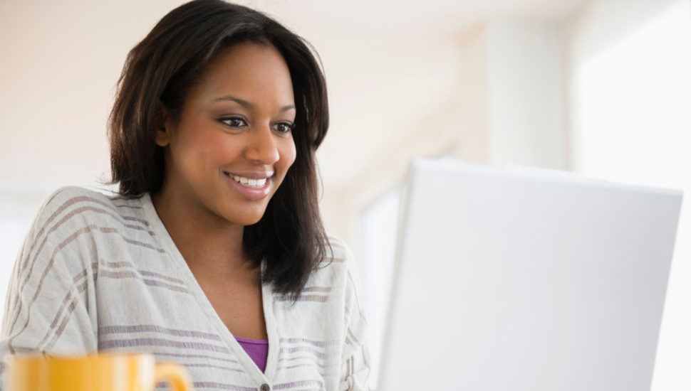 African American woman on computer for free webinar