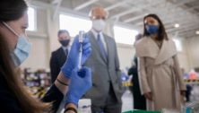 Pa. Gov. Tom Wolf and Acting Secretary of Health Alison Beam watch as Penn State Health vaccination clinic staff fill syringes of the COVID-19 vaccine.