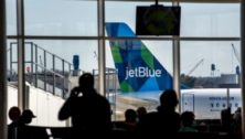 A JetBlue airplane is parked outside at the Philadelphia International Airport while people inside the terminal wait for their flight