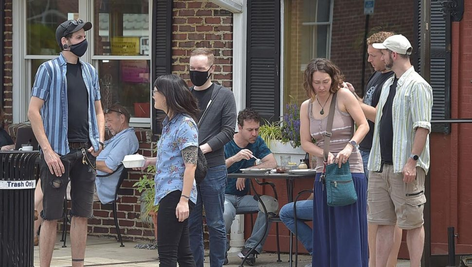 A scene of almost normal with masks and no masks outside the Corner Restaurant in Media.