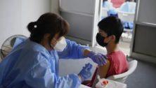 Nurse Hyun Lee administers a COVID-19 vaccine to Stephen Zeng, 15, of Northeast Philadelphia
