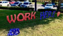 """A """"Work Here"""" sign on a lawn."""