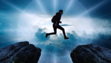 Man jumping from one mountaintop to another