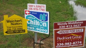 Several signs advertising homes for sale. Home prices are dropping.