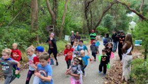 Children running in a 5K along a park path.