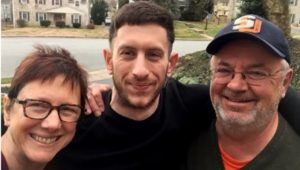 Thomas Kelly is seen in a Christmas 2019 family photo, with his parents, John Kelly and Christina Kimball-Kelly.