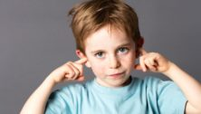 Boy plugging his ears.