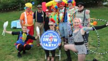 """Woman holds """"The Greatest Show on Earth"""" sign, surrounded by peoople dressed as circus performers."""