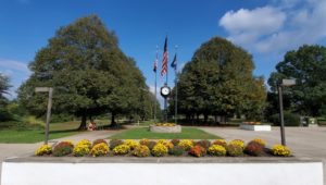 The pedestrian walkway with an American flag and planted flowers at Rose Tree Park